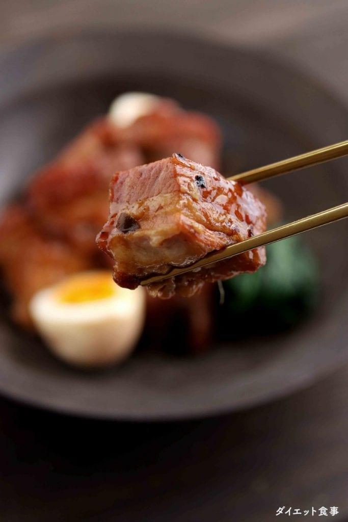 豚の角煮の一切れは箸で持っている写真